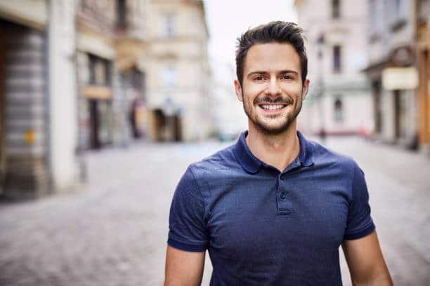 Homme en polo bleu marine qui sourie à la caméra