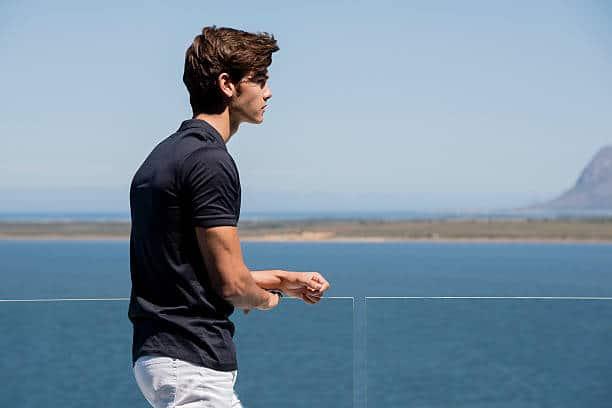 Jeune homme en polo noir et pantalon blanc qui regarde la mer
